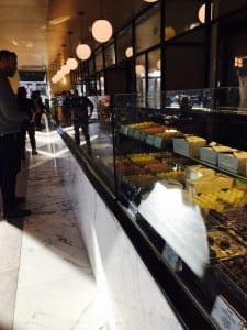 Inside of the French workshop with glass cases holding multiple desserts.