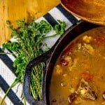 St. Kitts and Nevis Goat Water Stew in a cast iron dutch oven with parsley and thyme garnish