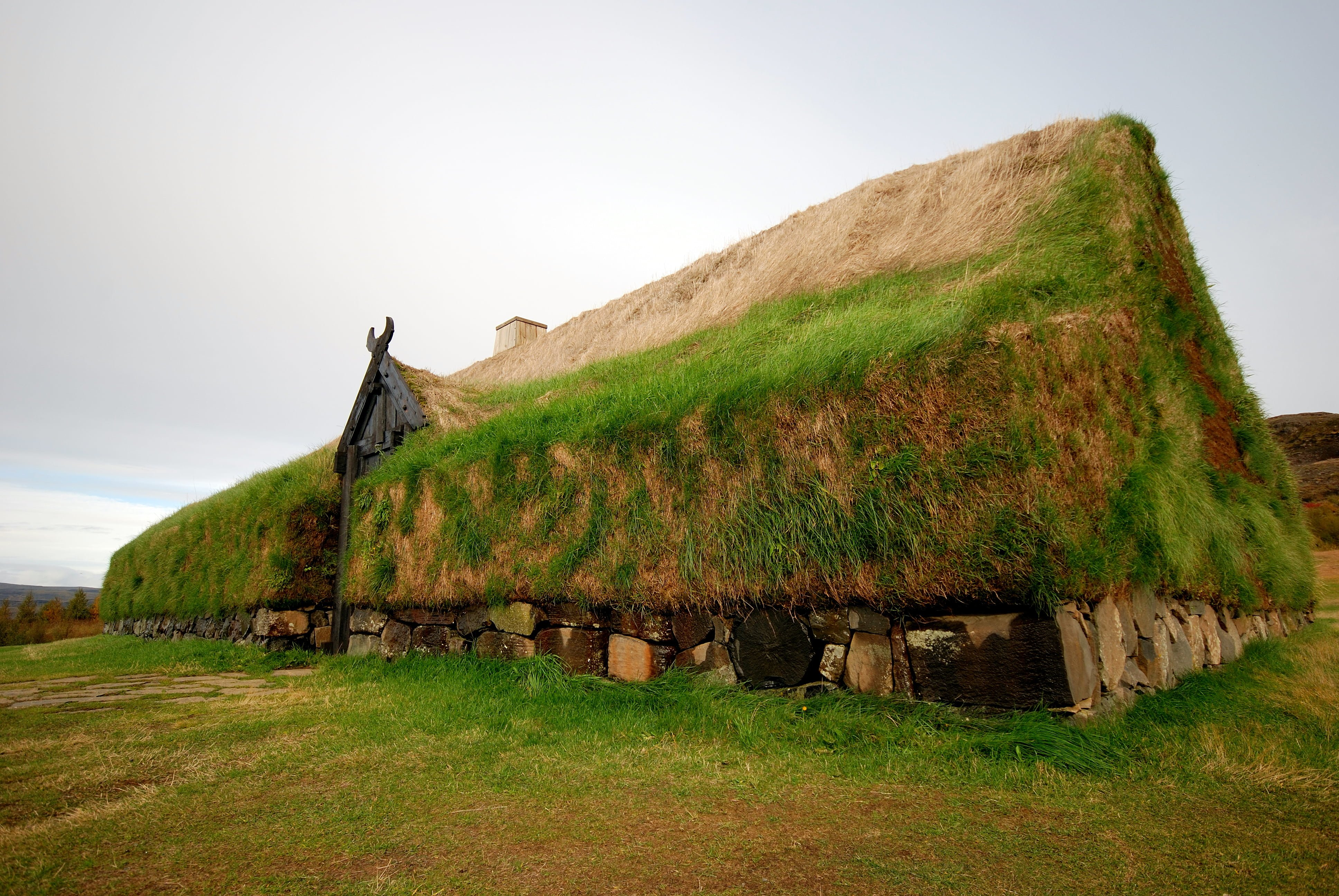 A photograph of Þjóðveldisbærinn in Iceland, a reconstruction of the Viking Longhouse Stöng. The building would have been the center of the farm of a Viking chief in middle ages and would have been used to store food. This replica adheres as closely as possible to the original way of building these longhouses, with a basic wood frame, stone base and turf walls/roof